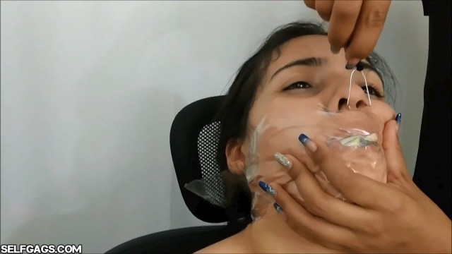 Mouth stuffed latina girl tied up and gagged with money and clear tape wrapped around her head