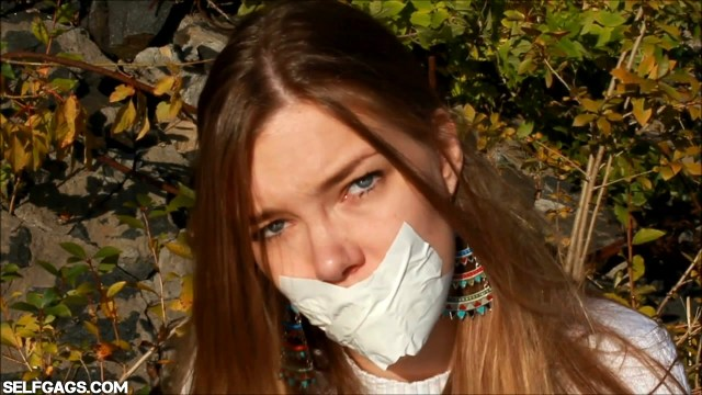Tape gagged girl is helpless outdoors