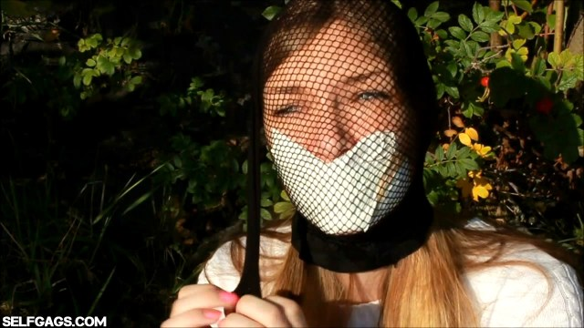Tape gagged model head encased with fishnet pantyhose outdoors