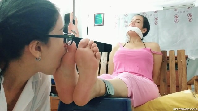Young girl with glasses worships feet of tape bound and cleave gagged latina milf