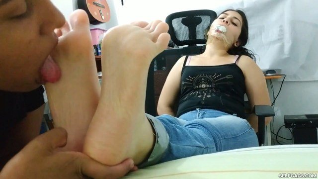 Sock gagged girl with tape around her mouth has her toes sucked by latina stepsister