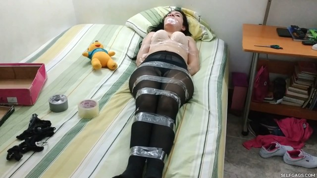Cute teenage girl wearing pantyhose is bound and gagged on her bed