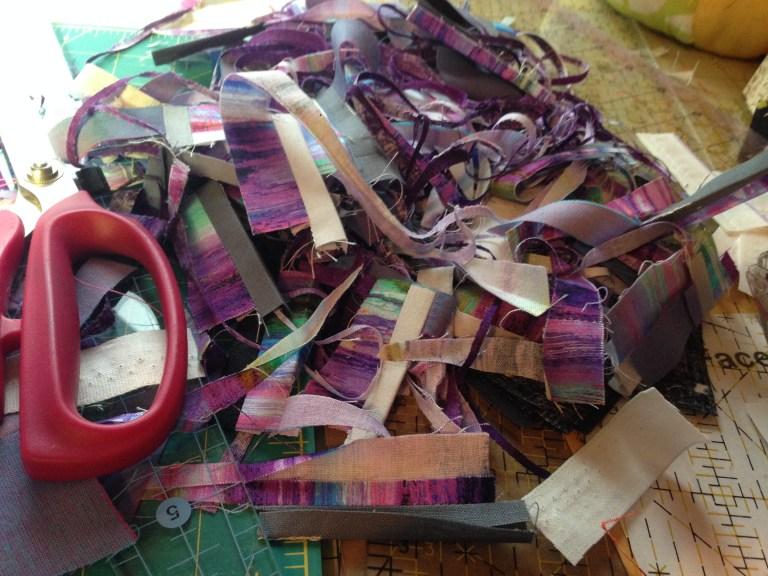 Purple fabric scraps piled on cutting mat