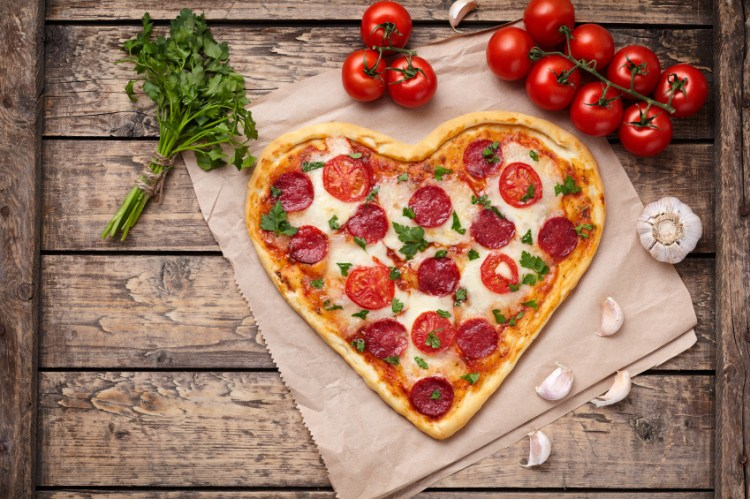Heart shaped pizza with pepperoni, tomatoes, mozzarella, garlic and parsley composition on vintage wooden table background.