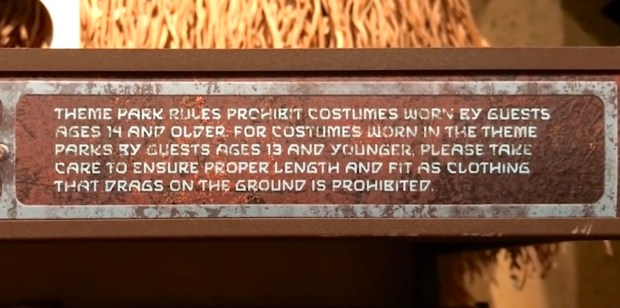 Signage next to Jedi robes in Galaxy's Edge: Theme park rules prohibit costumes worn by guests age 14 and older. For costumes worn in the theme parks by guests age 13 and younger, please take care to ensure proper length and fit as clothing that drags on the ground is prohibited.