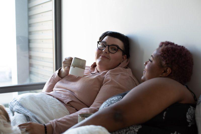 seksualnośc plus size niejedno ma imię: na zdjęciu dwie grube kobiety leżą w łóżku, patrząc sobie w oczy z czułością