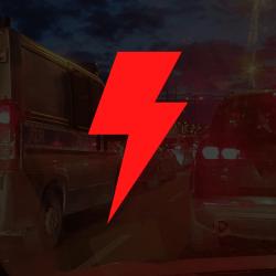 w tle zjęcie z samochodowej blokady miasta zrobione z wnętrza kabiny auta, na tym półprzezroczyste czarne tło z czerwoną błyskawicą na środku