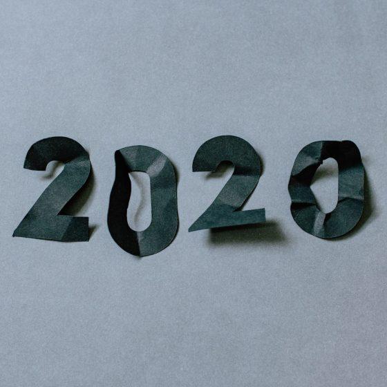 na szarym tle leżą wycięte z czarnego papieru, pogniecione cyfry układające się w numer roku 2020