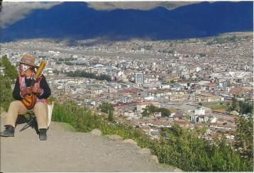 City overview with guy playing little guitar in Cusco
