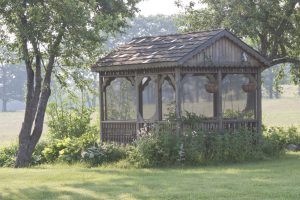 Screen House at Clary Lake Bed and Breakfast, Jefferson, Maine. Wooden screened gazebo before the Wisteria grew up to the roof and the other perennials grew taller than the sills.