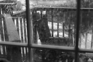 Black and White image of chair on porch behind rain spattered window.