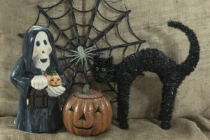 Halloween Still life composed of cute white ghost in black cape holding lamp and pumpkin, orange ceramic pumpkin, black cat with arched back and spider web with white spider against burlap backdrop.