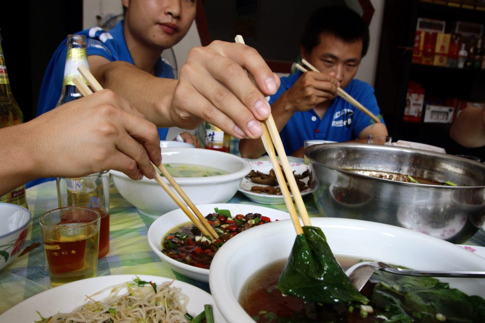 Diners eat lunch in a small restaurant in a village in souther Sichuan Province. Virtually all of the chopsticks found in the south of China are made from bamboo.