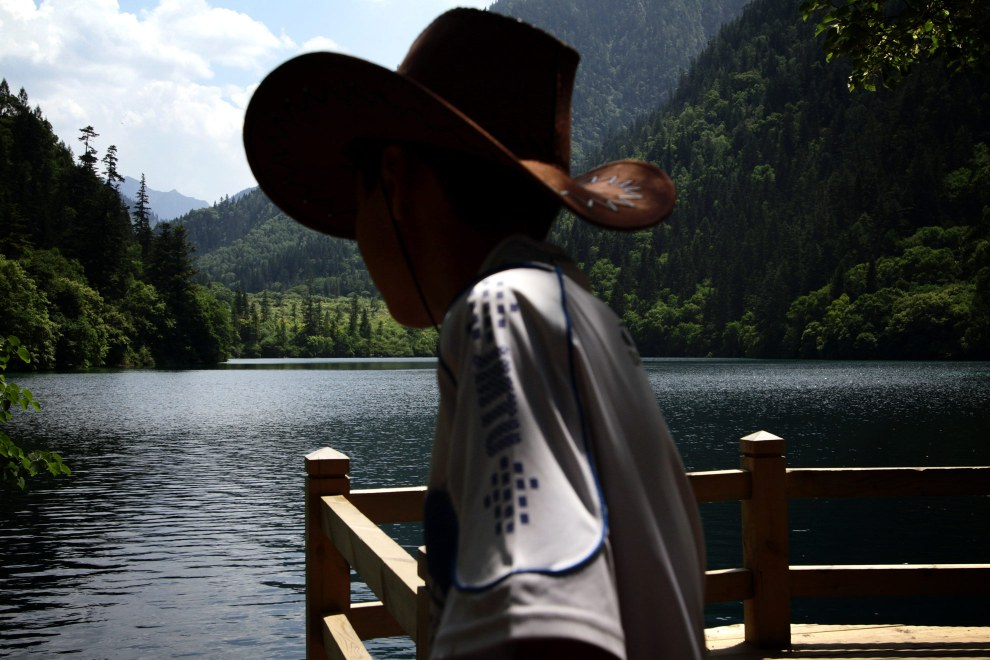 A young boy in a cowboy hat looks out onto one of the many lakes that make up the Jiuzhaigou Nature Reserve in northern Sichuan.