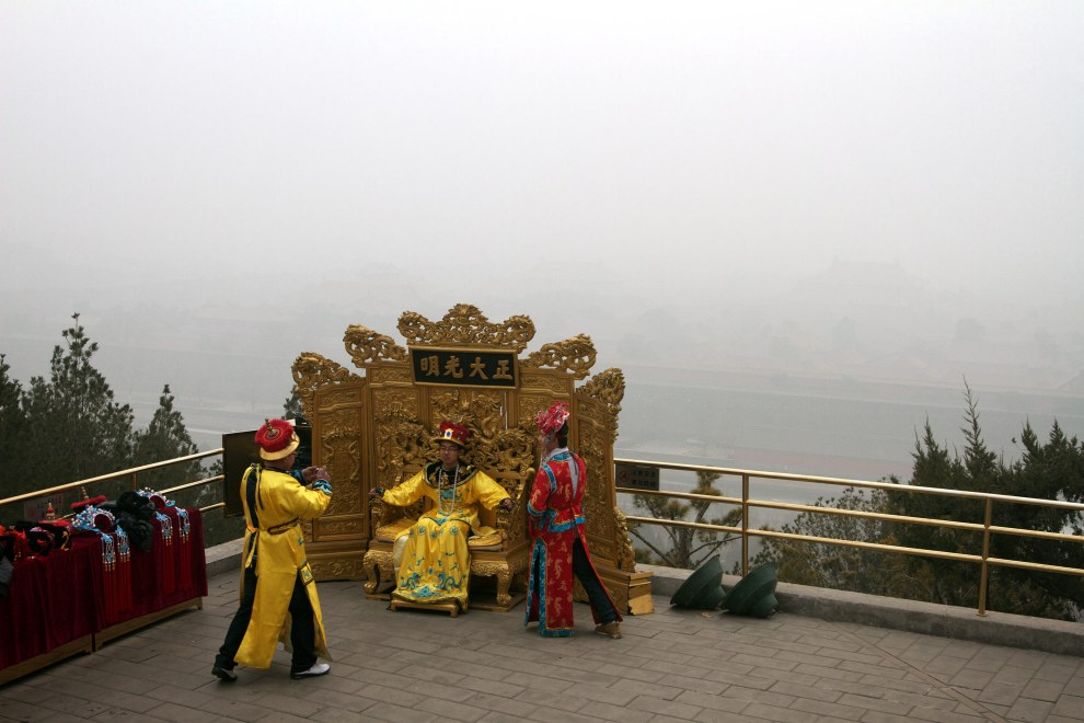 Young men pose for pictures on Coal Hill in central Beijing, China. Air pollution obscures the view of the Forbidden City behind them.