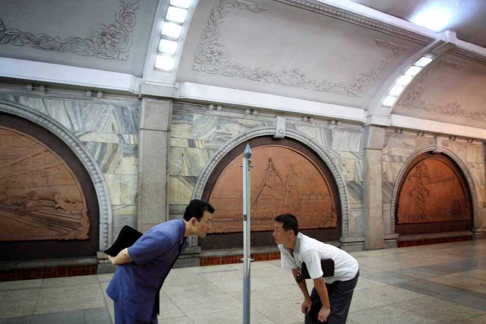 North Korean men read a timetable in a subway station in Pyongyang.