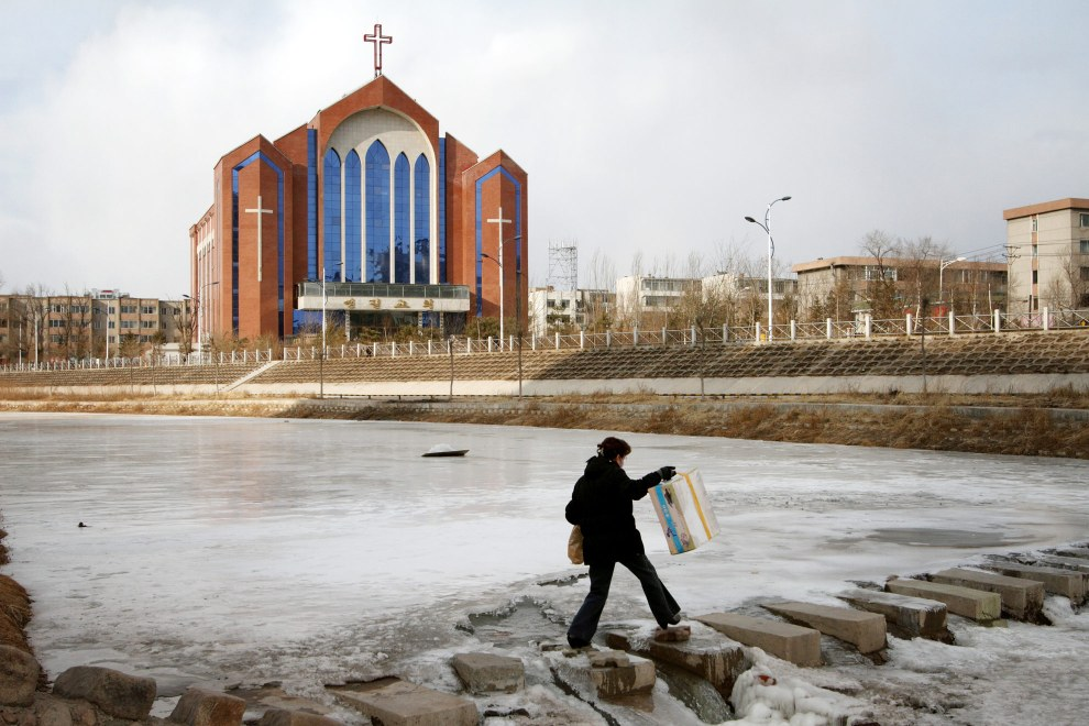 A woman crosses a river in the town of Yanji, close to the border with North Korea. The town is part of the Korean Autonomous Prefecture in the north-east of the country. Christianity is prevalent in the region and churches can be seen in major towns.