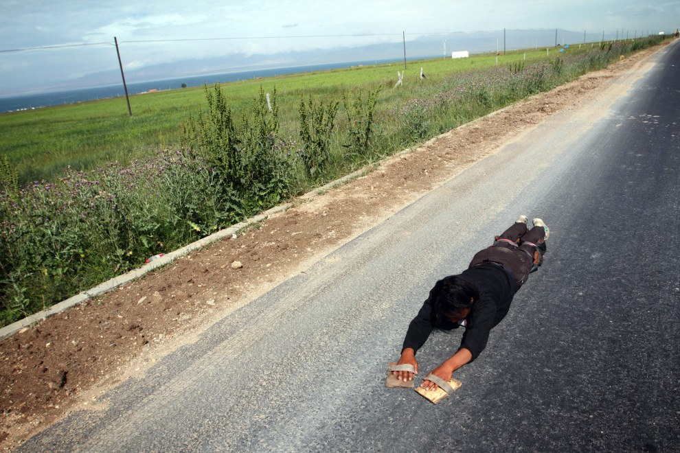"""Tenzin (27), a young Tibetan man prostrating around Qinghai Lake. The lake is sacred to Qinghai Tibetans and according to Tenzin, """"by circling it seven times, we can clear our sins and wrongdoings."""""""