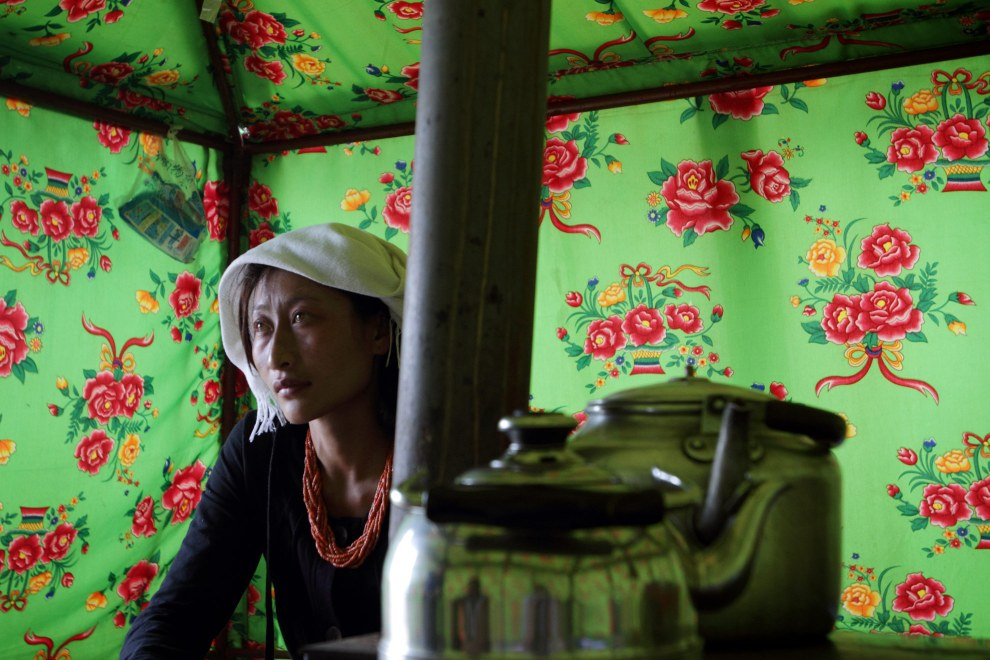 A young Tibetan woman in her tent near the shores of Qinghai Lake. She and her husband are nomdic herders who spend winters in the mountains and summers next to the lake.