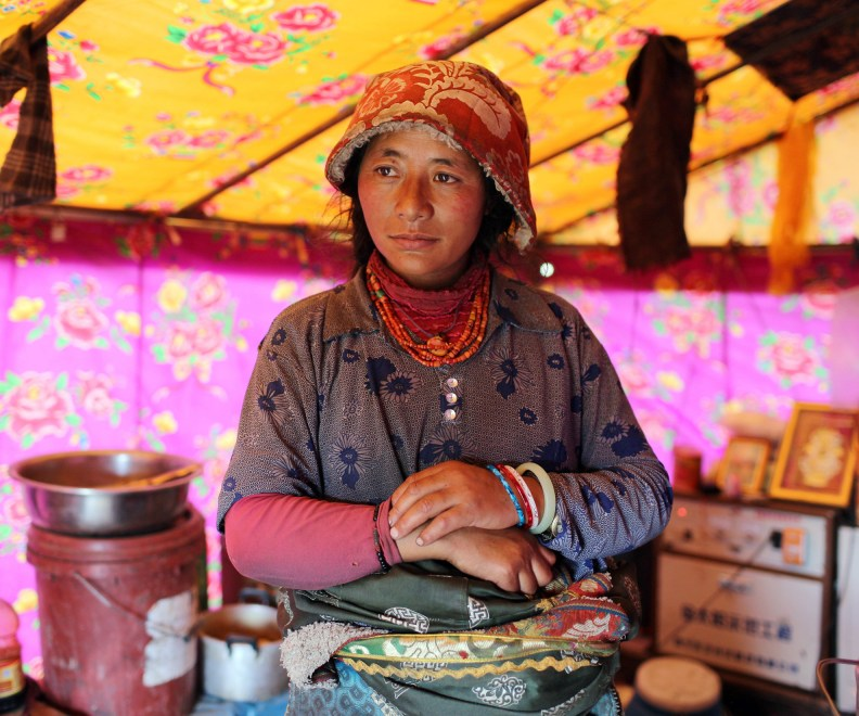A Tibetan nomad stands inside her traditional tent on the grasslands of the Amdo region on the Tibetan Plateau.