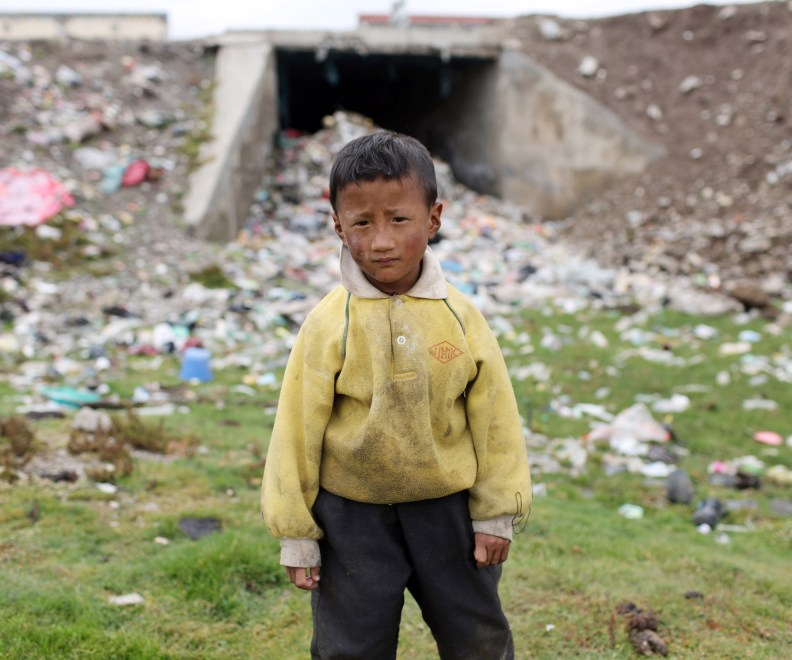 A young Tibetan boy stands near piles of refuse in a town on the Tibetan Plateau.