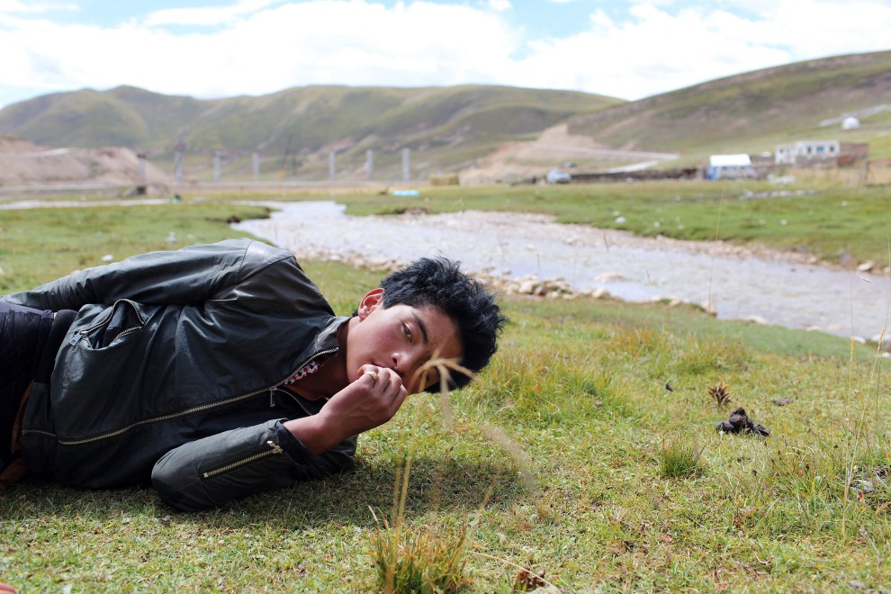 A young Tibetan man lies on the grassland of his family farm in the Sanjiangyuan or Three Rivers Headwater region of western China. The region contains the sources of the Yangtze, Mekong and Yellow Rivers.