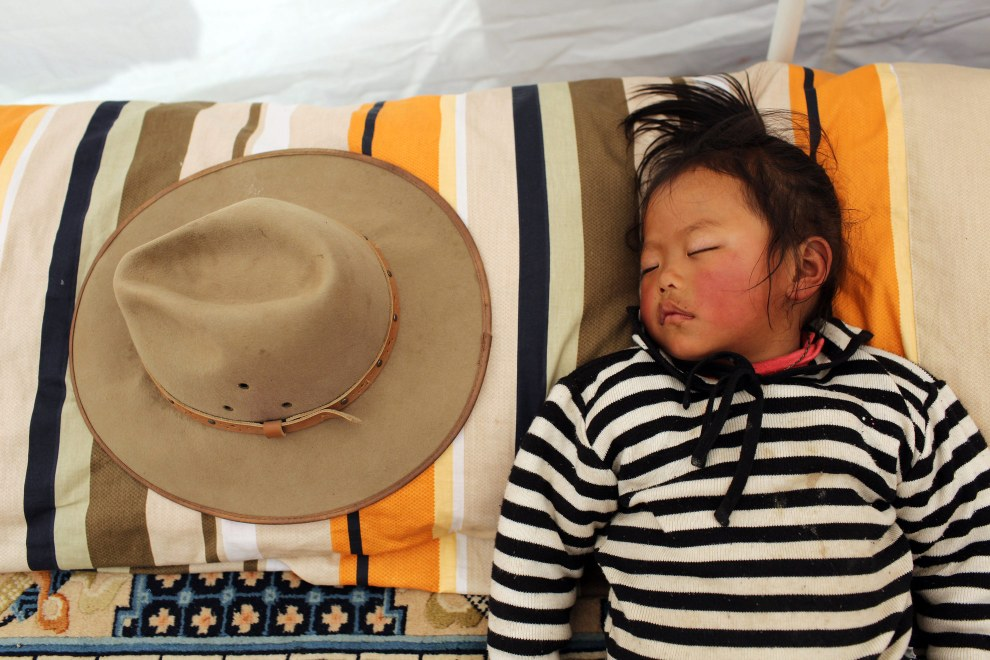 A child sleeps in her family's tent on the grasslands of the Tibetan Plateau. Few nomads remain in the region, as many have been relocated into towns as part of large-scale relocation projects.