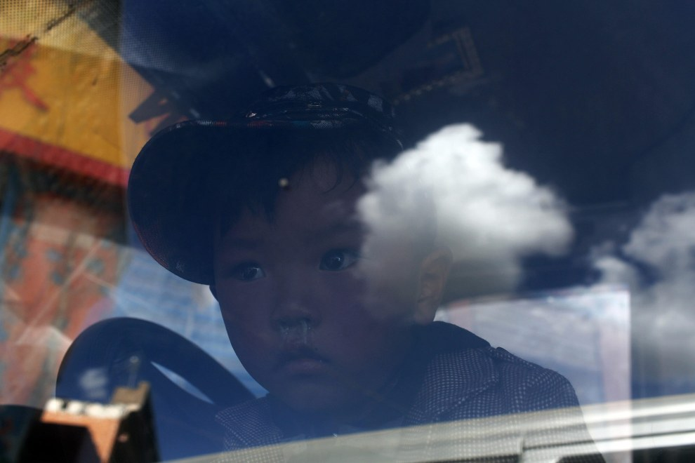 A Tibetan boy looks out of a car window and onto the blue skies of the Tibetan Plateau.