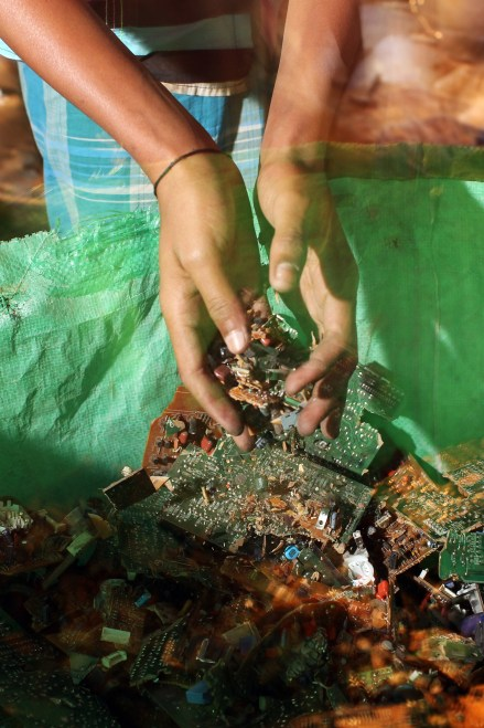 A electronics waste recycler handles circuit boards which have been partially dismantled. Lead, mercury, arsenic and other toxic elements are released in the breakdown process and workers often have little to no safety equipment to protect themselves.