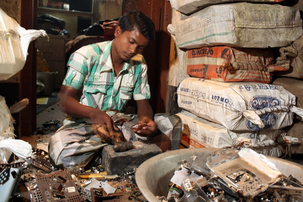 In the village of Sangrampur, south of Kolkata, a villager breaks down and sorts through various types of E-Waste.