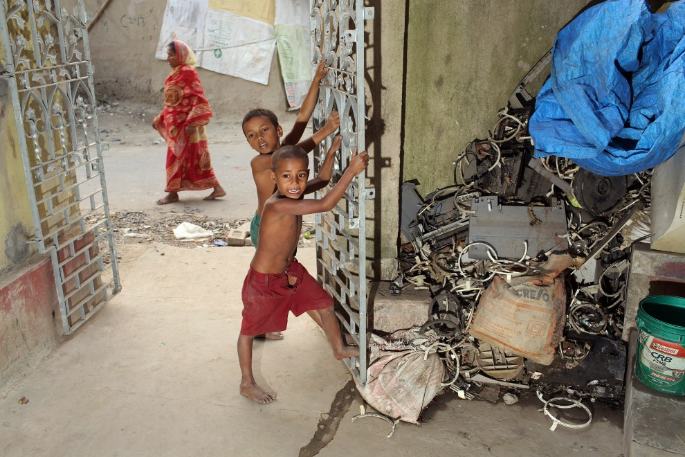 Children play barefoot near discarded piles of E-Waste. Lead, mercury, arsenic and other toxic elements are released in the breakdown process of E-Waste and often enter nearby local communities and homes.