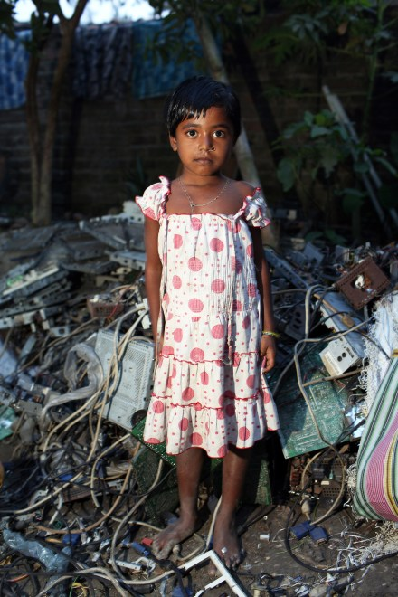 A young girl stands barefoot near piles of E-Waste in the village of Sangrampur near Kolkata. Lead, mercury, arsenic and other toxic elements are released in the breakdown process and those who handle the waste have little to protect themselves from the harmful materials.
