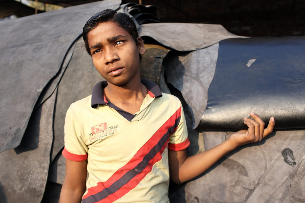 Rakesh, 16, strokes a piece of leather in the factory where he works in the India city of Kanpur. He suddenly lost the sight in his left eye as a child and is one of many people in the area suffering from health development issues.