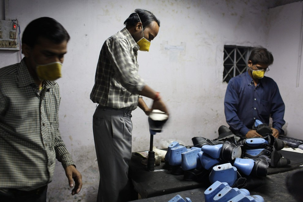 Factory workers making leather shoes in a workshop in the Jajmau area of Kanpur.