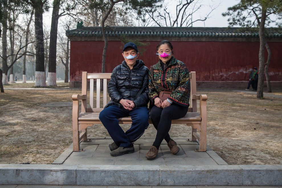 """Mr. Liu (56) and Mrs. Wang (54), a married couple in Beijing, sit on a bench in the capital's Ditan Park. Their unique pollution masks are designed to filter air breathed through the nose, with exhalation then from the mouth. They are one of the new types of masks now appearing as alternatives to the traditional face mask. """"We started using these one month ago"""", explains Mr. Liu. """"This one is more comfortable. It filters out 95% of the pollution."""" PM2.5 reading - 367 - Hazardous"""