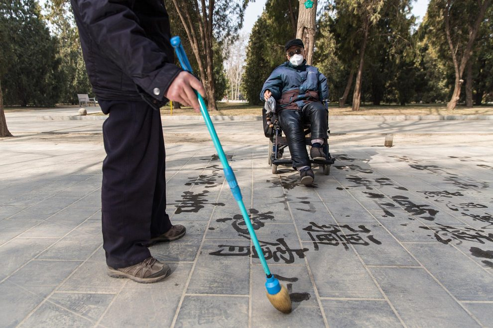 An elderly man in a wheelchair watches a fellow Beijinger draw Chinese characters with water into the dusty pavement. PM2.5 reading - 367 - Hazardous