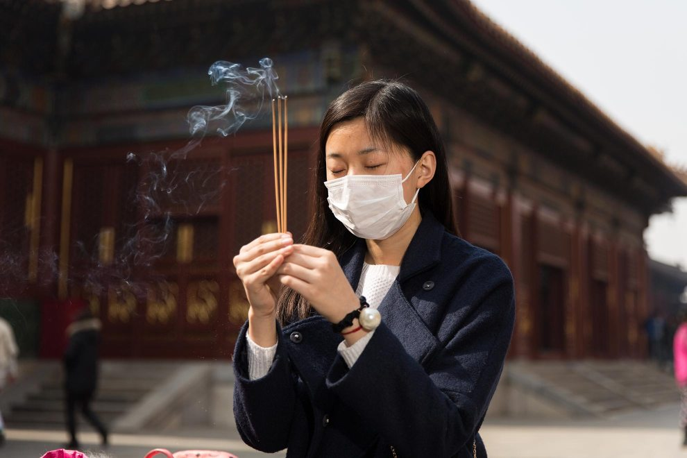 """Ms. Zeng (21), a student, burns incense while making wishes at a shrine inside Beijing's Lama Temple. """"I think the weather is bad. I started using the mask about one year ago because of the pollution."""" PM2.5 reading - 261 - Very Unhealthy"""