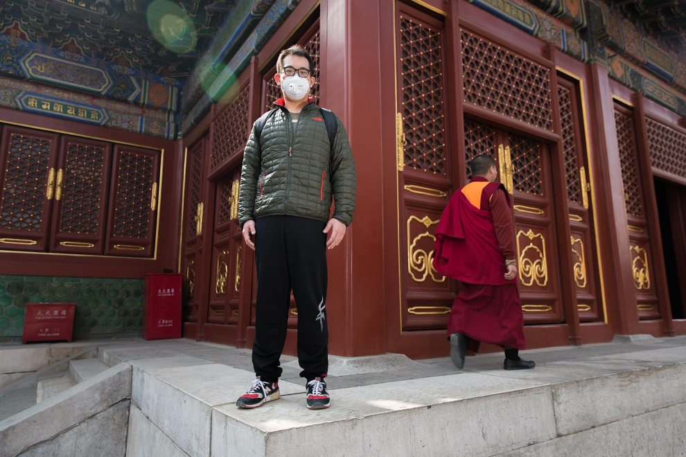 """Xue (29), an engineer visiting Beijing's Lama Temple. """"Of course it's not comfortable but we have to put it [the mask] on. I wore it earlier than most. I started about 4 years ago. I cough when I smell the dust."""" PM2.5 reading - 200 - Unhealthy"""