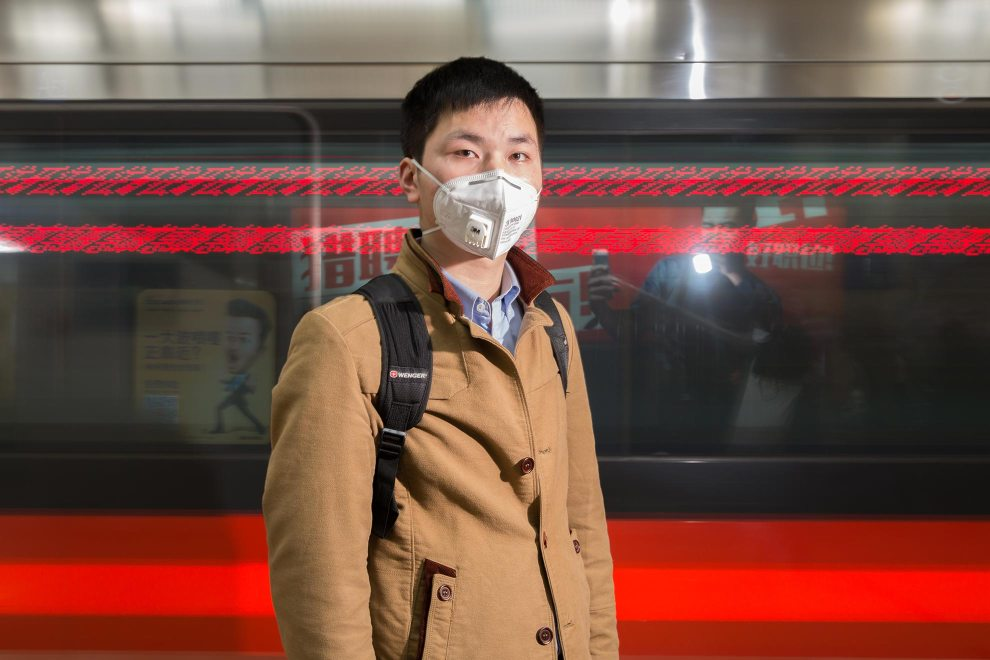 """Li (23), a sales worker from Hebei Province stands on the platform in Beijing's subway system. Many residents now not only wear the masks outdoors but also in indoor public spaces and on public transportation. """"The pollution is too much. I have worn [the mask] since 2013. My home city, Shijiazhuang, is more polluted!"""" PM2.5 reading - 191 - Unhealthy"""