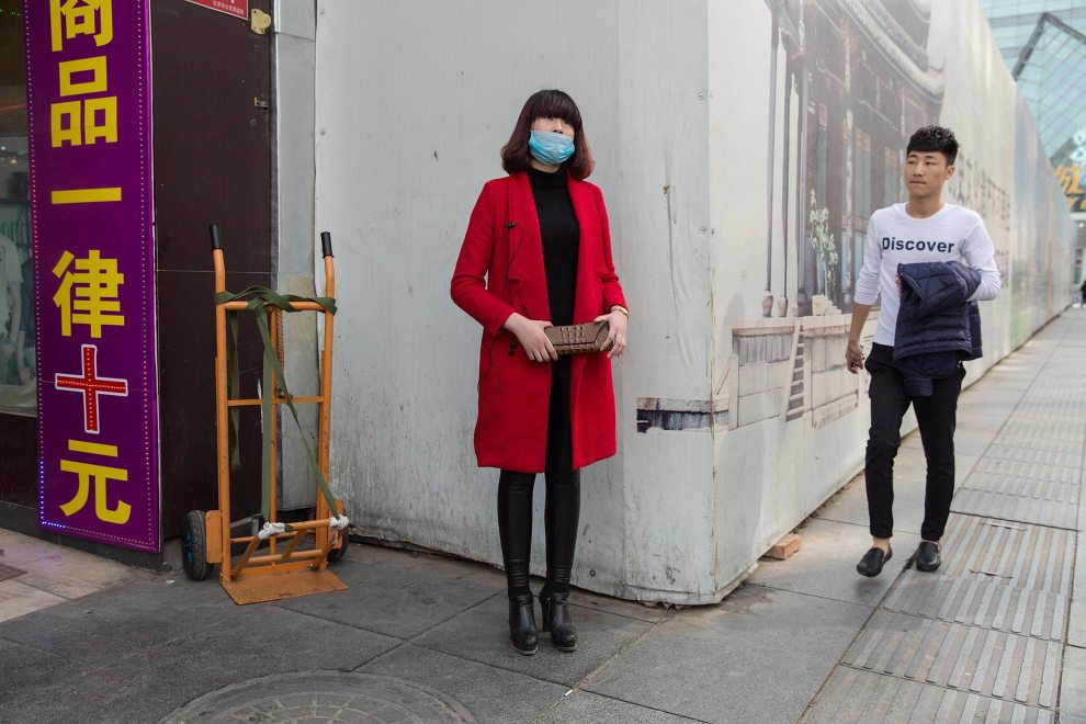 """Li, a 17-year old beautician from Shandong province, stands in Beijing's Xidan shopping district. """"I study here in Beijing. The air is bad""""' she says. """"Two years ago I started wearing [the mask]. It helps protect my skin. There are too many people here in China which has ruined the environment.""""  PM2.5 reading - 102 - Unhealthy for Sensitive Groups"""