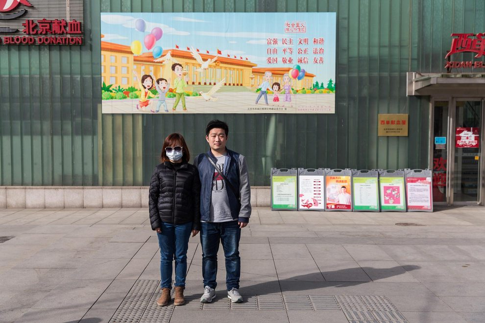 A couple, Ms. Hu (27) and Mr. Teng (27), stand underneath a propaganda poster depicting an idyllic Beijing life, in the city's Xidan shopping district. PM2.5 reading - 102 - Unhealthy for Sensitive Groups
