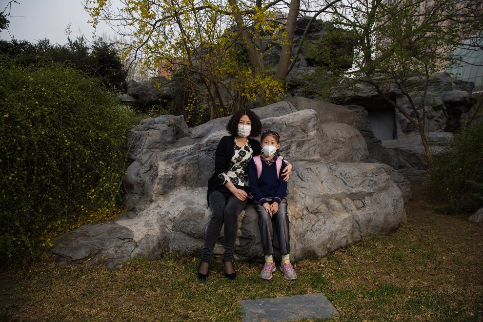 """Mrs. Liu sits with her daughter in a small garden outside of her office in the west of Beijing. """"I want to protect my daughter. She's young. She isn't able to protect herself"""", she explains as to why she makes her daughter wear a mask. """"I'm sure the PM2.5 is bad for people's health. I'm thinking of sending her overseas. I think it will take a long time to clear the air. I don't want my daughter to have to live with this situation."""" PM2.5 reading - 204 - Very Unhealthy"""