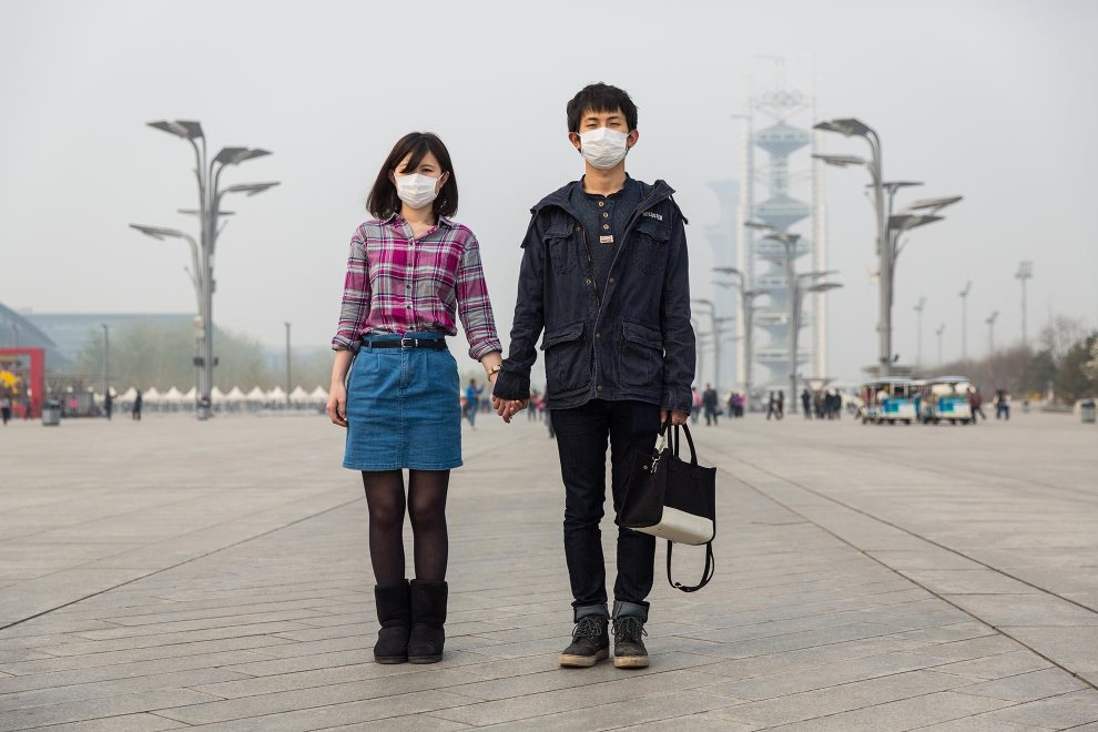 "A young couple, Ms. Lu and Mr. Li, hold hands during a walk through Beijing's Olympic Park. ""I'm pretty sad about this. It's worse and worse"", explains Li. ""I think the pollution is bad for our health. The PM2.5 damages our lungs [but] we don't have any choice"", he laments. ""I left China two and half years ago. Then it wasn't so bad. I've been abroad. I know what's good [air] and what's bad. Young people care more than old people. We have more information. We know how bad it is."" PM2.5 reading - 218 - Very Unhealthy"