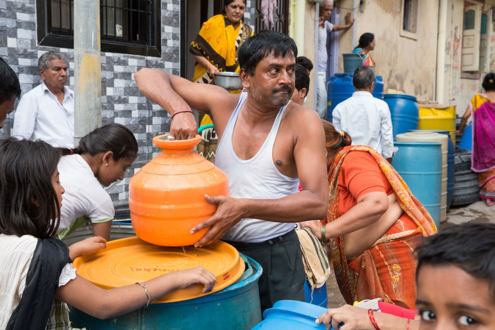 A man prepares to pick up a container full of water that he has just filled from freshly delivered government water trucks. The trucks visit many of the city's communities delivering water to those in need. Crowds regularly develop and arguments often ensue as the city's desperate residents make sure they receive enough water.