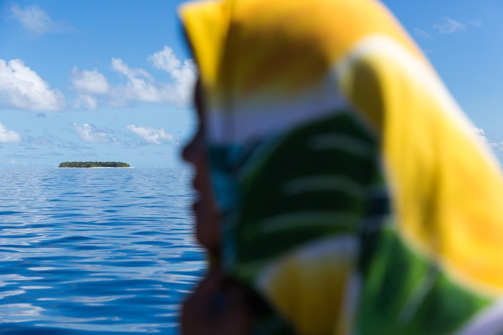 A Tuvaluan woman looks out from a boat as it passes through the Funafuti atoll, Tuvalu.