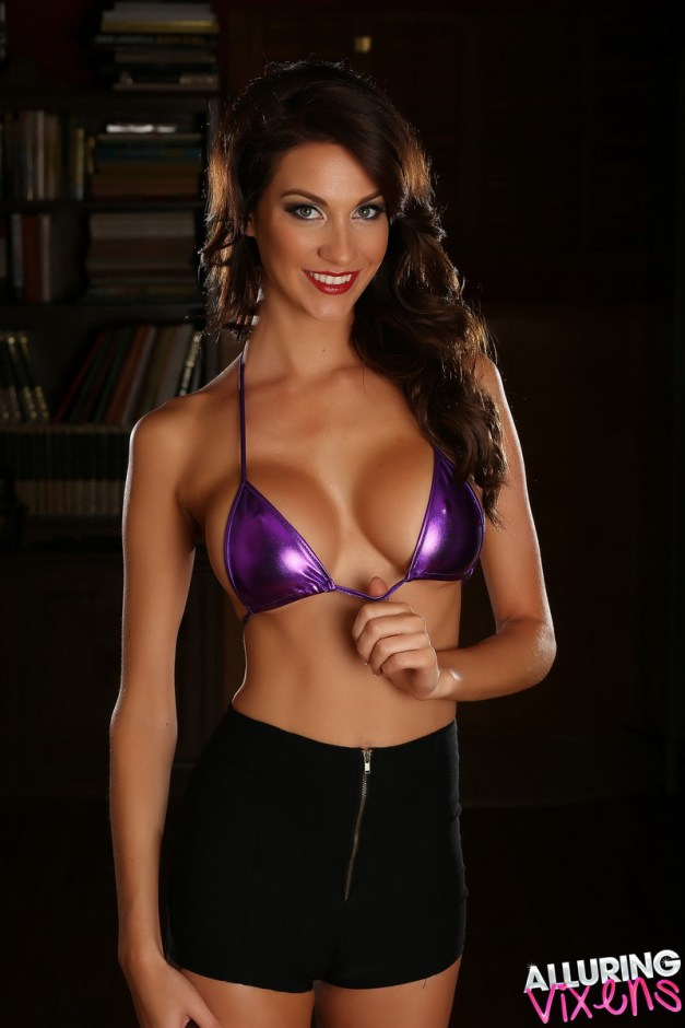 Stunning busty Alluring Vixen tease Bethany shows off her big boobs in a skimpy shiny purple string bikini top
