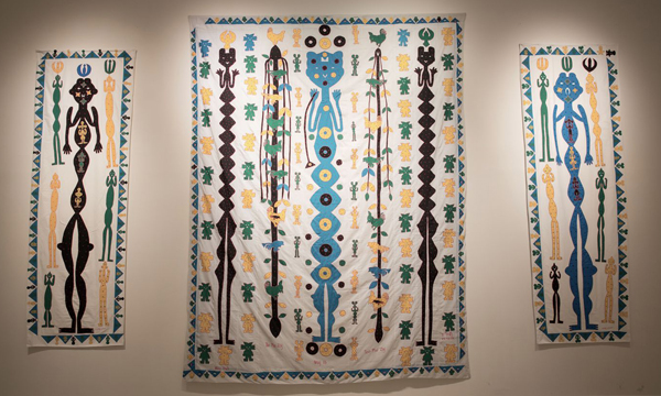 geometric style humanoid figures on printed/sewn wall hangings