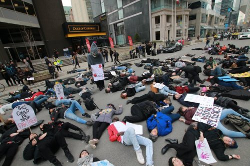 the group marched south on University stopping at Queen to lie down in a mock die-in in the middle of the street. They lay there for several minutes stopping traffic. Onlookers stood frozen by the display.