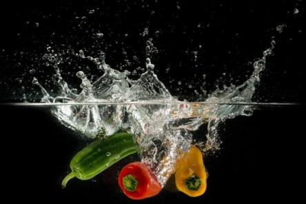 Red and yellow peppers and zuccini splashing into water.