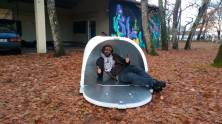 Photo of a man smiling at the camera inside an iglou which is a white foam tube with an aluminum lining.